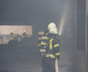 Zwei Kameraden bei Brandbekämpfung in verrauchter Halle