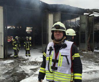 Feuerwehrangehörige vor der ausgebrannten Halle