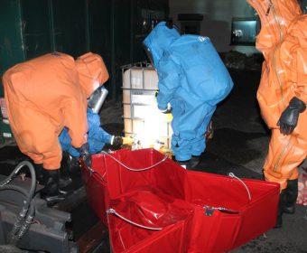 Angriffstrupps unter Chemikalienschutzanzügen beim Abdichten