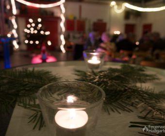 Kerze mit Weihnachtsbaum im Hintergrund