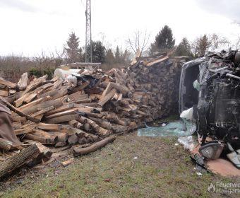 Zerstörtes Kfz vor Holzstapel