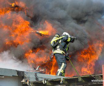Gebäudekomplex im Vollbrand mit Feuerwehrmann im Vordergrund